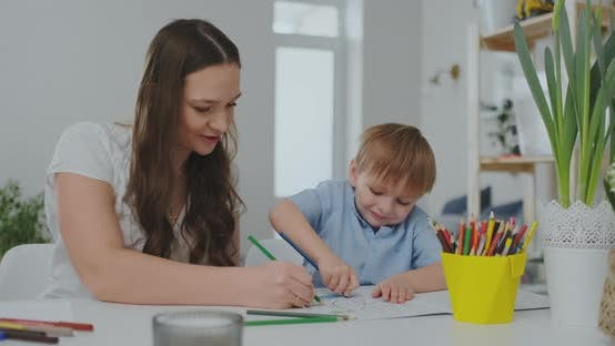 Thumbnail for A Family of Two Children and a Young Mother Sitting at the Table Draws on Paper with Colored Pencils