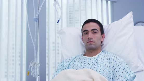 Thumbnail for Adult male latino patient lying on hospital bed and looking at camera