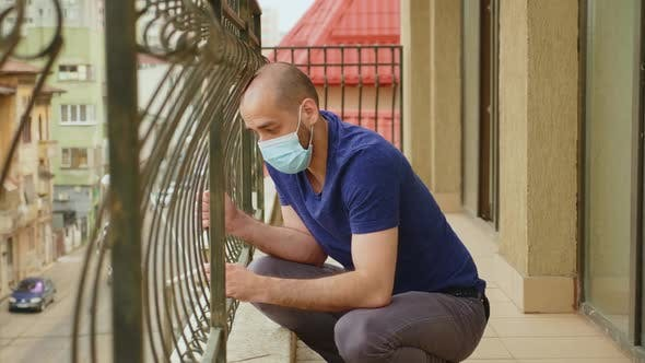 Depressed Man on Balcony of His Apartment