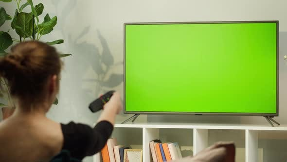Woman Watching TV with Green Screen in Living Room Back View