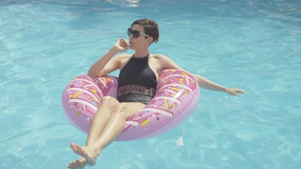 Young Wealthy Brunette Woman Sitting on Donut Swimming Ring and Sucking Lollipop. Wide Shot of