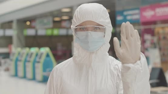 Thumbnail for Female Airport Employee in Protective Eyeglasses, Antiviral Suit and Face Mask Making Stop Gesture