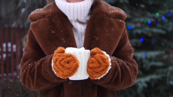 Thumbnail for Female Hands In Knitted Gloves Holding Cup Of Cocoa Outdoors