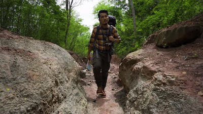 man traveler with backpack walking and looking in the natural forest