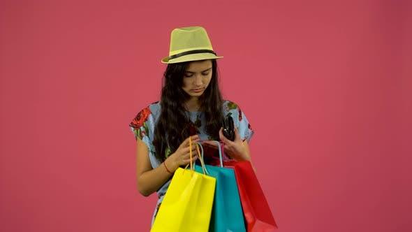 Thumbnail for Mädchen sieht in Einkaufstaschen, dann hat die Geldbörse das Geld ausgegangen, aber es gibt eine Karte