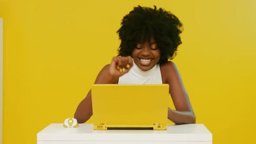 Pretty African Woman Uses Yellow Laptop