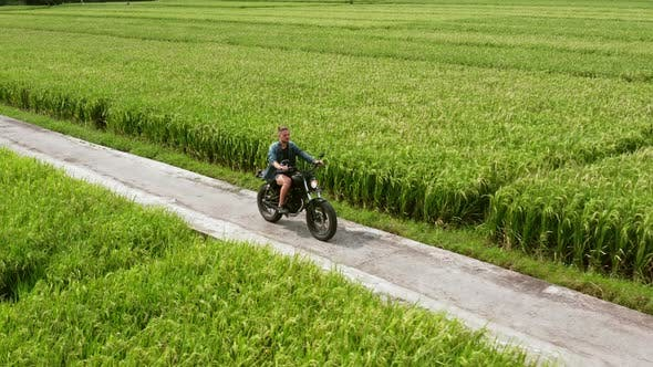 Motorcycle Driver Riding on a the Rice Fields. Outdoor Shot, Countryside Landscape. Travel and Sport