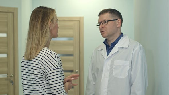 Male doctor talking to young woman patient in the hospital hall