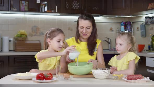 Mama und ihre zwei Töchter haben Spaß in der Küche. Mama lehrt Kinder, wie man Pizza macht. Glückliche Mutter