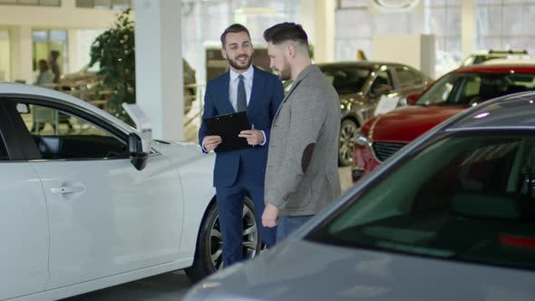 Thumbnail for Auto Salesman Showing Car to Male Client