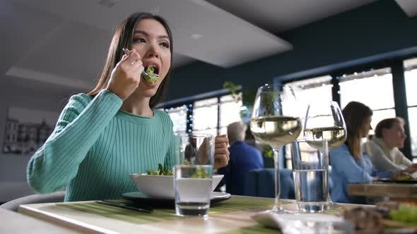 Asian Woman Eating and Communicating in Restaurant
