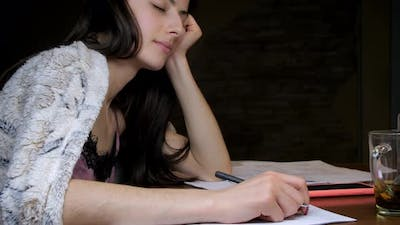 Long Haired Student with Pen Naps Holding Head on Hand