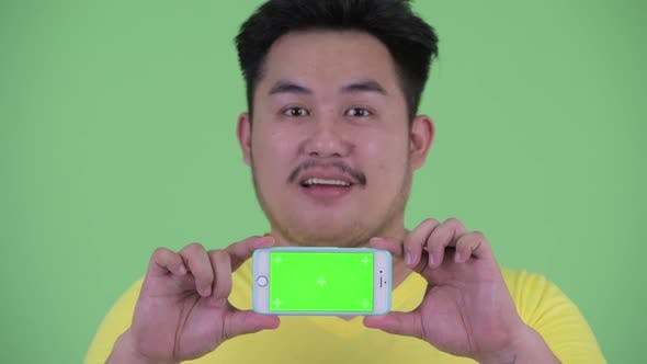 Thumbnail for Face of Happy Young Overweight Asian Man Thinking While Showing Phone