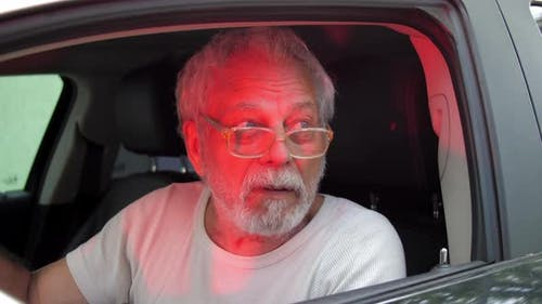 Old Man Talks with Serious Face Under Flashing Lights