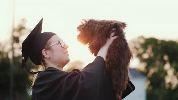 Cover Image for A Young Woman in a Graduate Costume Holds a Cute Puppy in Her Arms