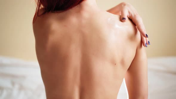 View from Back Slim Woman Applying Moisturizer Cream Body Lotion on Her Shoulder