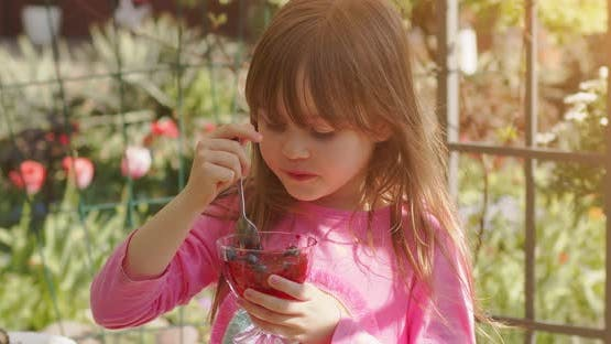 Cute Little 6 or 7 Years Old Girl Eating Fruit Dessert Jelly in Summer Garden