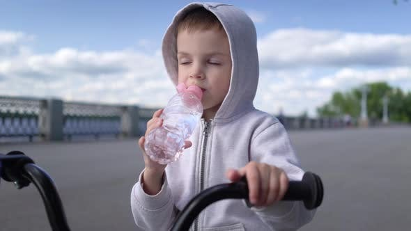 Cover Image for Boy Child Learning To Ride First Running Balance Bike and Drink Water