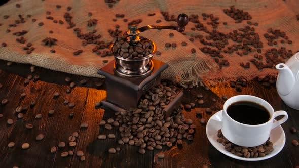 Teekanne und Tasse Kaffee auf Untertasse mit Kaffeekörnern