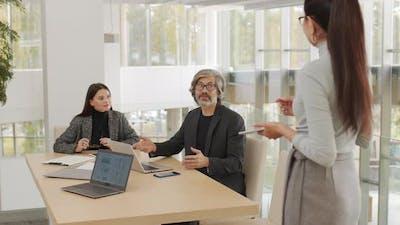 Coworkers Negotiating In Meeting Room
