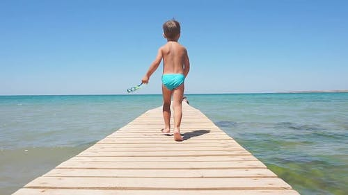 Happy Boy, a Child Walking Along the Sea Pier Towards the Azure Sea, Slow Motion. Sunny Summer Day
