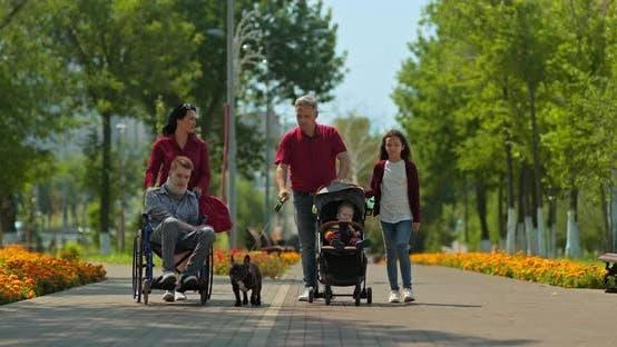 Große Familie mit einem Kleinkind und einem behinderten Teenager geht durch den Park. Behinderter Kerl ist Sein