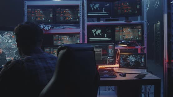 Hacker Watching Multiple Monitors