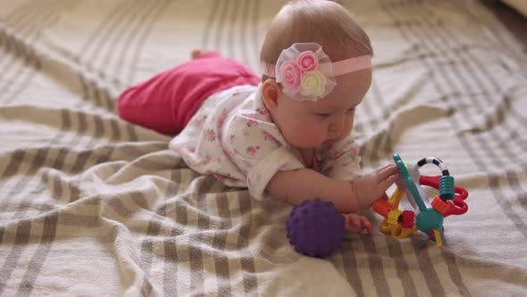 Thumbnail for Cute Baby Girl Playing with Toy Ball on Floor