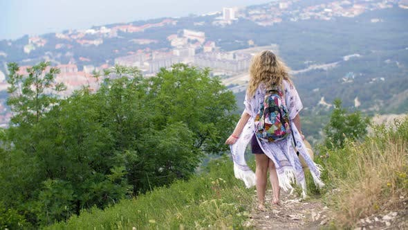 Thumbnail for Tourist Woman with Backpack Walking Down on Mountain Path on City Panorama View, Traveling Woman