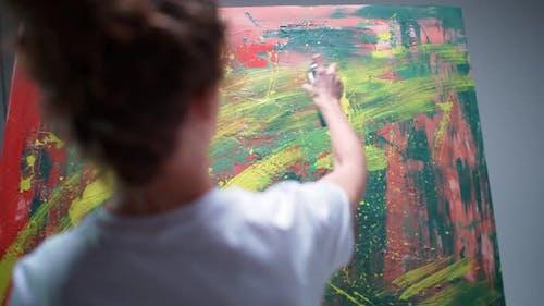 Une artiste féminine dessine avec de la peinture en aérosol sur une grande toile dans une pièce blanche une artiste talentueuse