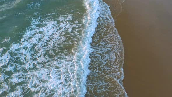 Aerial shot of waves breaking on the beach.