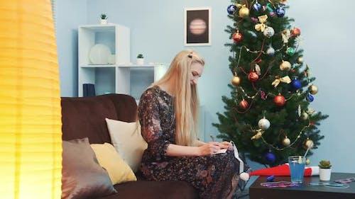 Pretty Woman Writing a Postcard Near the Christmas Tree