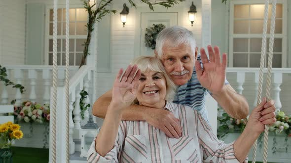 Thumbnail for Senior Elderly Couple in Front Yard at Home. Man Hugging Woman. Happy Mature Family Waving Hands