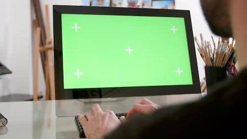 Man Types Continuously in Front of a Green Screen