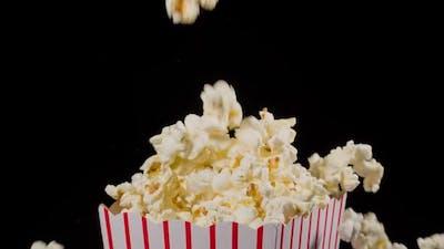 Popcorn falling in slow motion into a popcorn bucket