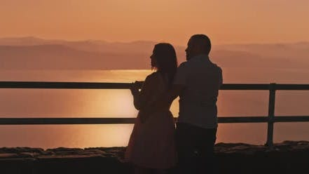 Thumbnail for Young couple watching sunset above the lake from the viewing point, Medium shot