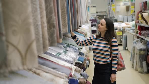 Young Woman Choosing a Curtain in Textile Shop