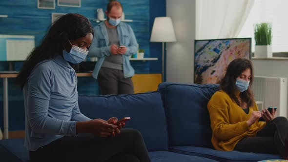 Mixed Racial People Sitting Together in Living Room Browsing on Phones