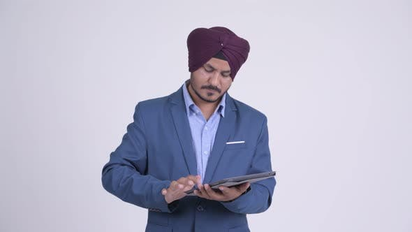 Thumbnail for Happy Bearded Indian Sikh Businessman Thinking While Using Digital Tablet
