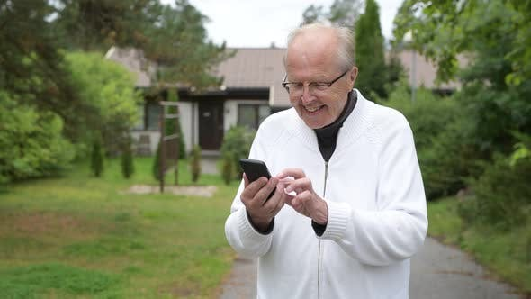 Thumbnail for Happy Senior Man Smiling While Using Phone At Home Outdoors