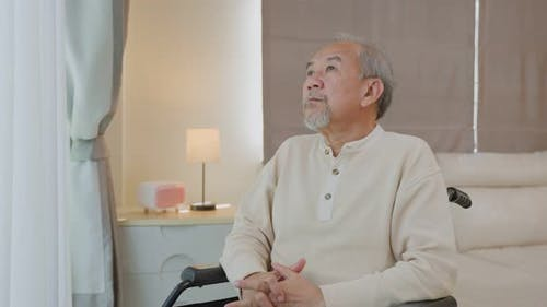 Asian Senior Elderly male sit alone on wheelchair, feel lonely and worry from health care problem.