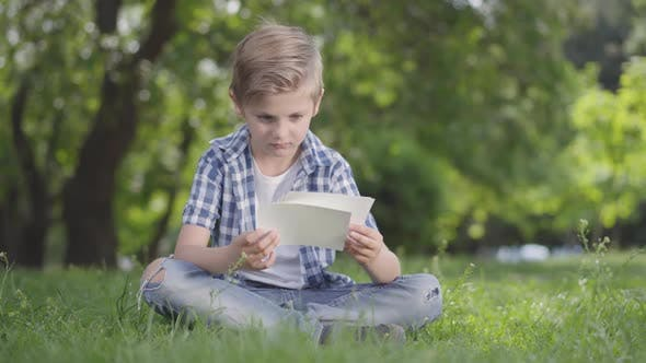 Thumbnail for Portrait of Adorable Cute Boy in Checkered Shirt Looking at the Sheets of Paper in the Park