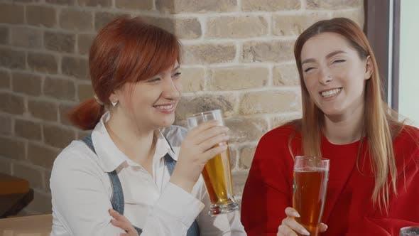 Zwei junge Frauen klirren zusammen in der Bar mit Biergläsern