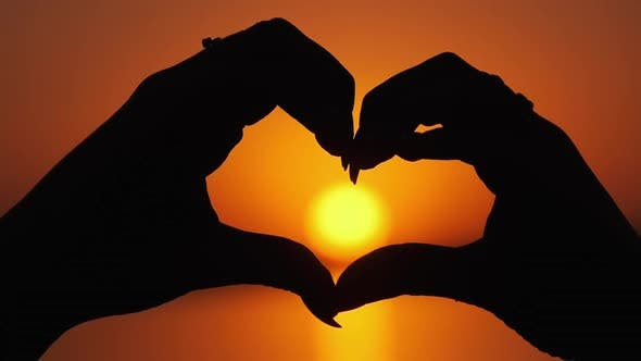 Thumbnail for Silhouette of Female Hands Holding Sign in the Shape of a Heart at Orange Sunset