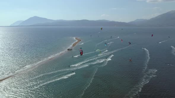 Aerial view of big group kitesurfing close to the shore.