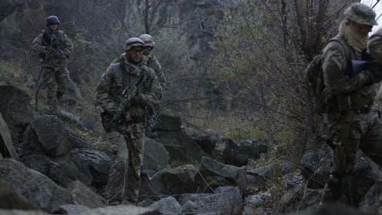 Thumbnail for Armed Soldiers Walking Through Rocks at Dusk