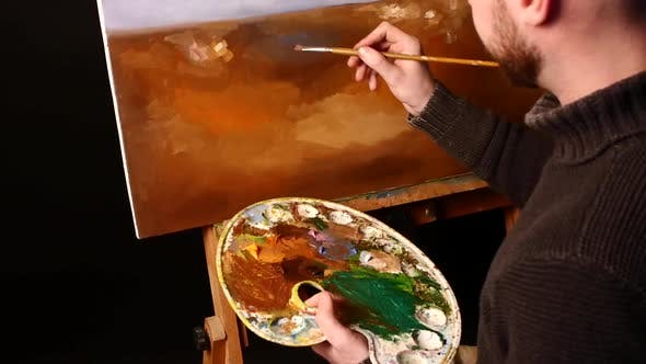 Thumbnail for Talanted Painter, Dark Sweater Starts Drawing an Object on Painting By Oil Paints Holding the