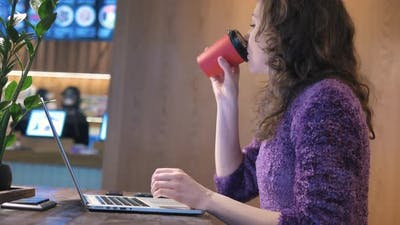 Slim Young Woman Drinks Coffee and Works on Laptop in Cafe