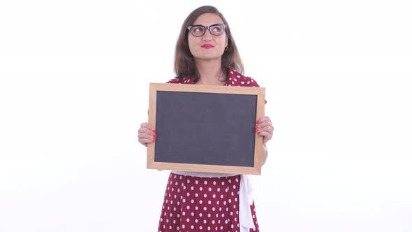 Thumbnail for Happy Beautiful Woman with Eyeglasses Thinking While Holding Blackboard
