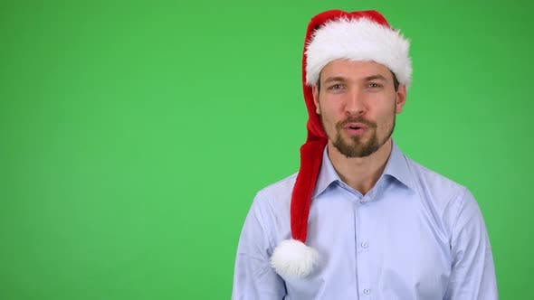 Thumbnail for A Young Handsome Man in a Christmas Hat Talks To the Camera with a Smile - Green Screen Studio